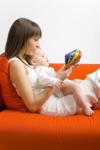 Mother, baby reading cloth book on sofa dreamstime_m_2555688